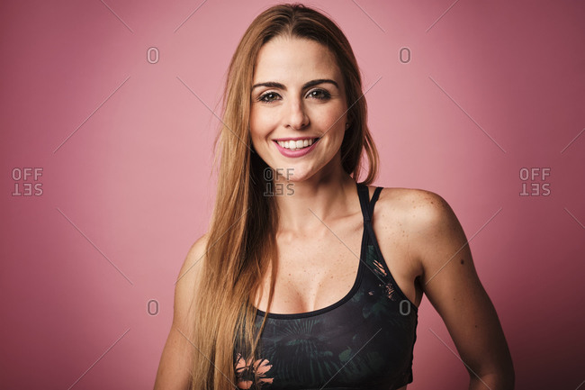 Blond girl wearing sport clothes in front of a pink background while looking at camera with a big smile