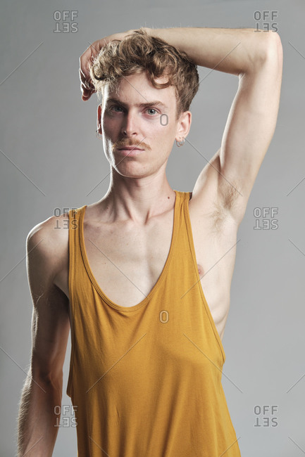 Young blonde man with mustache and a yellow t-shirt looking at camera with his arm on his head