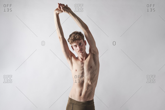 Young bare chested blonde man with mustache stretching his arms looking at camera