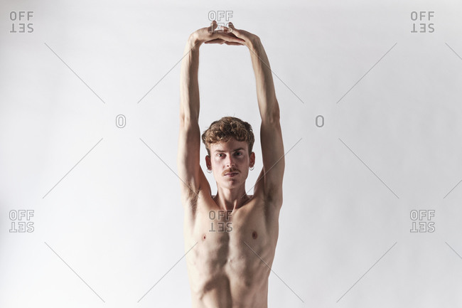 Bare chested blonde man with mustache stretching his arms looking at camera