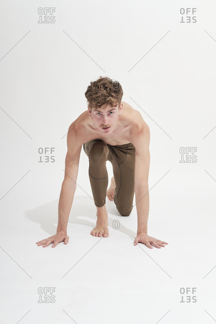 Frontal view of a young blonde man stretching on white background