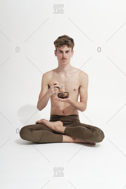 Young blonde man resting on the floor with a Tibetan bowl in lotus position