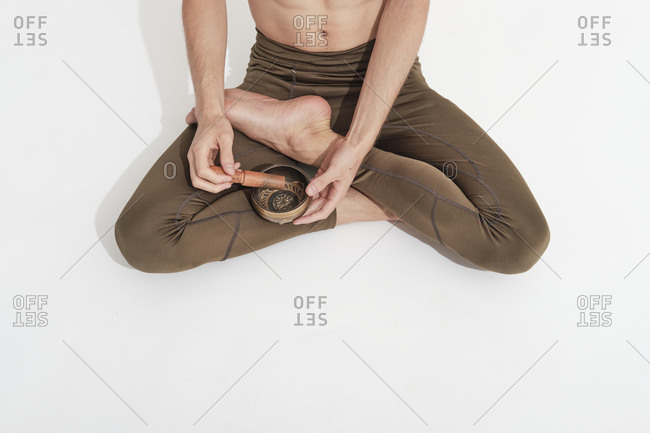 Young man resting on the floor with a Tibetan bowl in lotus position