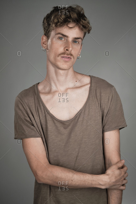 Portrait of a young blonde man with blue eyes and mustache wearing a brown scoop neck shirt