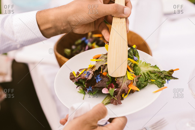 Person serving themselves salad with edible flowers