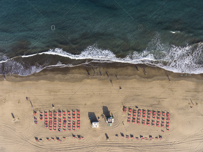 Bird's eye view of beach filled with red lounge chairs on the coast of the Ocean