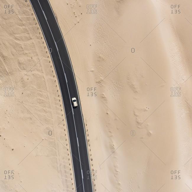 Car driving on highway through sand dunes