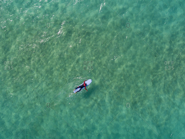 Bird's eye view of a surfer in the blue ocean waters