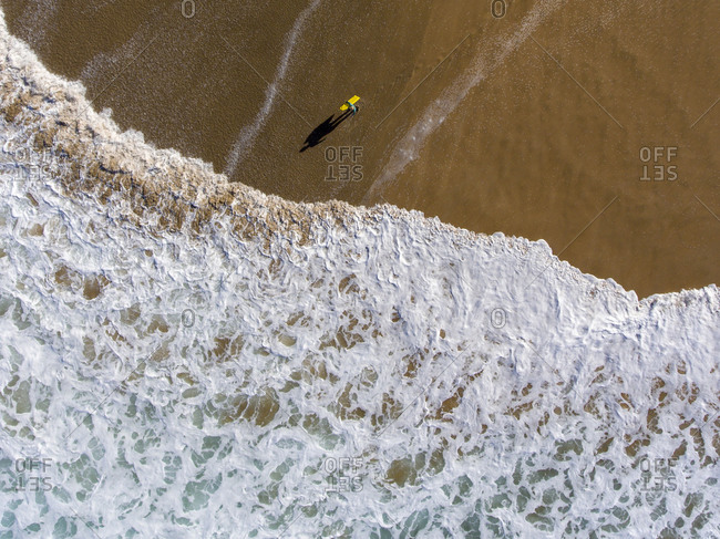 Body surfer going into the ocean viewed from above