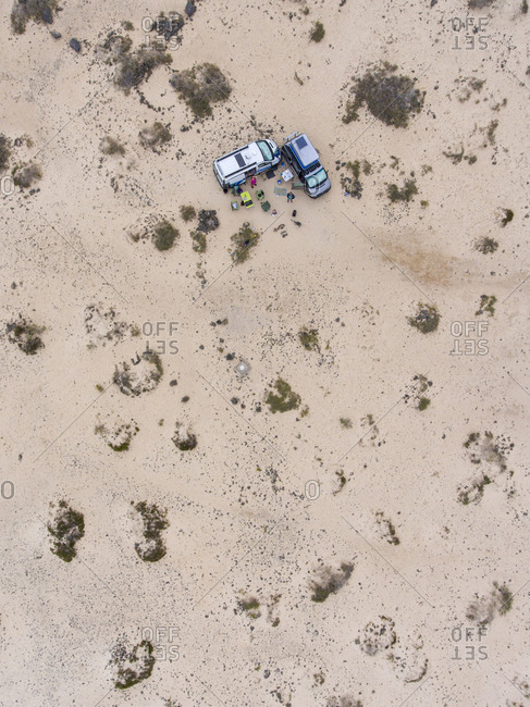 People camping with campervans in the sand dunes seen from above