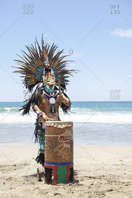 Sayulita, Mexico - June 15, 2018: Man playing drum dressed in full Native American costume