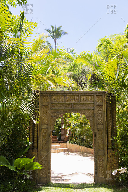 Archway surrounded by lush green palms
