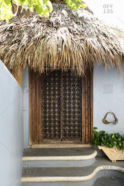 Wooden entrance on blue house with a thatch roof