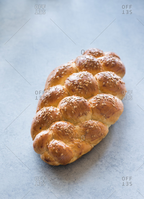 Homemade challah bread with sesame seeds over grey background