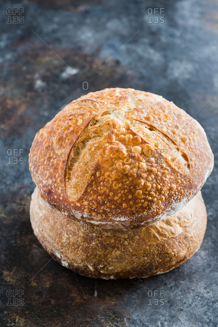 A loaf of wheat homemade sourdough bread on dark background