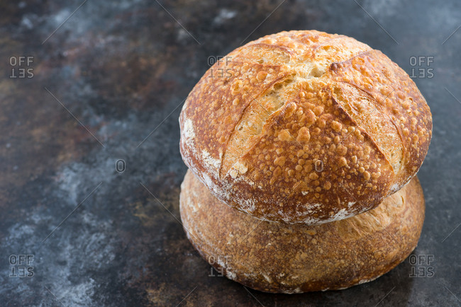 Close up of a loaf of wheat homemade sourdough bread on dark background