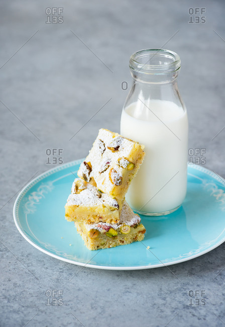 Lemon bars with pistachio nuts on plate with bottle of milk on grey background
