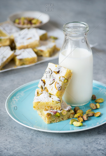 Lemon bars with pistachio nuts on plate with bottle of milk on a blue plate