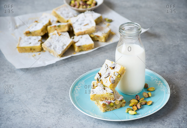 Lemon bars with pistachio nuts on plate with bottle of milk on a blue plate and gray background