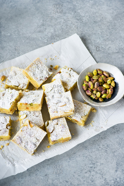 Lemon bars with pistachio nuts on parchment paper over gray background