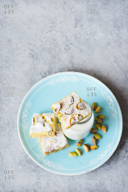 Overhead view of lemon bars with pistachio nuts on plate with bottle of milk on a blue plate