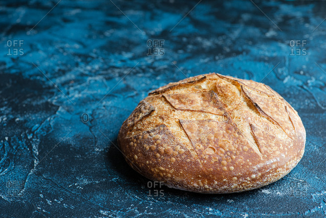 Loaf of homemade sourdough bread on blue background