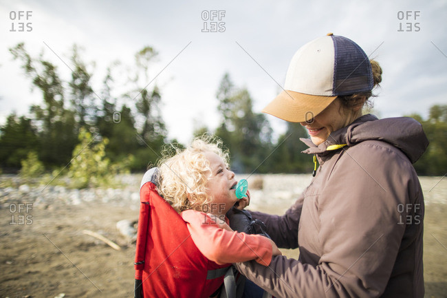 Mother putting crying son in baby carrier