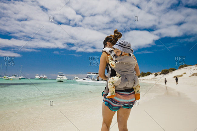 Mother on beach with baby in baby carrier, Rottnest Island, Western Australia, Australia