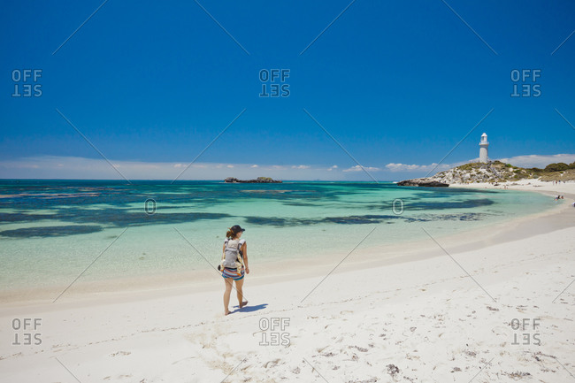 Mother with son in baby carrier on beach, Western Australia, Australia