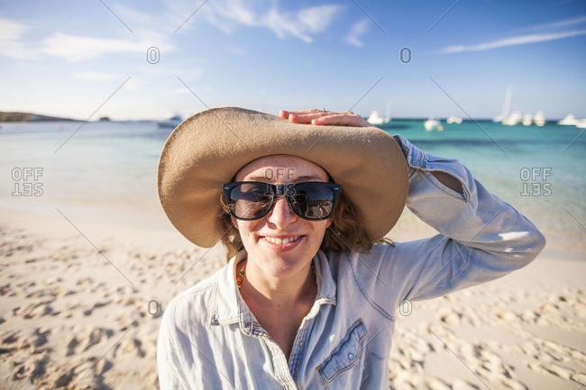Portrait of woman in hat on beach, Perth, Western Australia, Australia