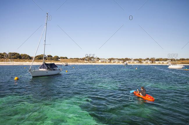 Woman kayaking near sailboat, Long reach Bay, Rottnest Island, Western Australia, Australia