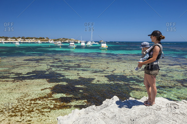 Mother carrying baby in baby carrier looking at yachts sailing near coast, Perth, Western Australia, Australia