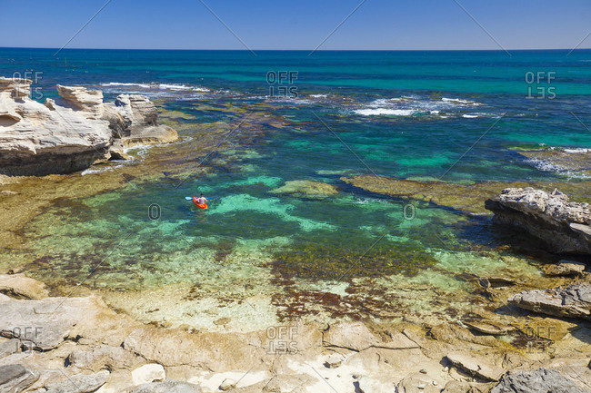 Woman kayaking around Basin of Rottnest Island, Perth, Western Australia, Australia
