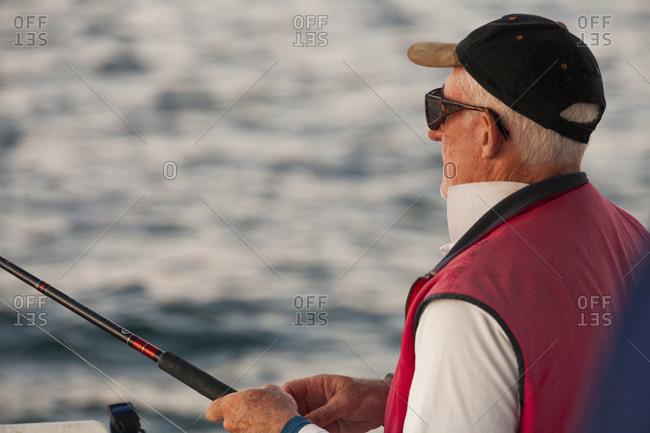 Sailor fishing off back of sailboat in Long reach Bay, Perth, Western Australia, Australia