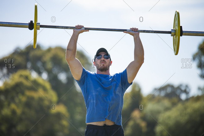 Man lifting weights outdoors to get strong