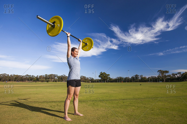 Woman weightlifting outdoors to gain strength