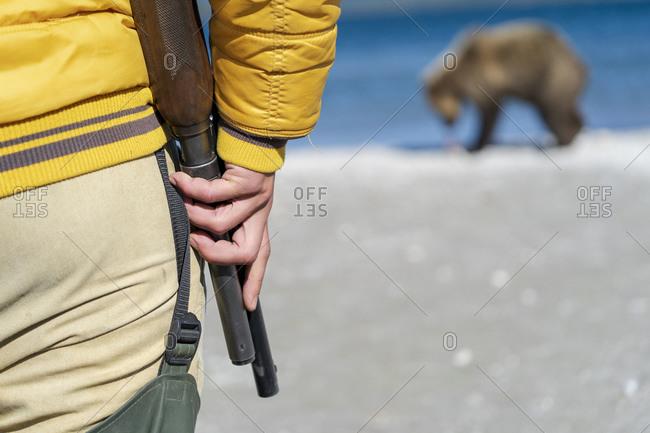 Park ranger with shotgun watching brown bear, Kurile Lake, Kamchatka Peninsula, Russia