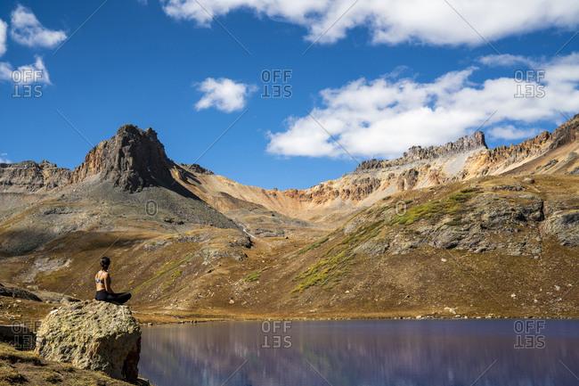 Woman sitting on rock on shore of Blue Lake, San Juan Mountains, Colorado, USA