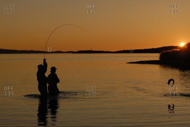 Men fishing at sunset, Katmai National Park, Alaska, USA