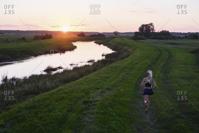 Woman trail running along Leba River, Pomerania Province, Poland