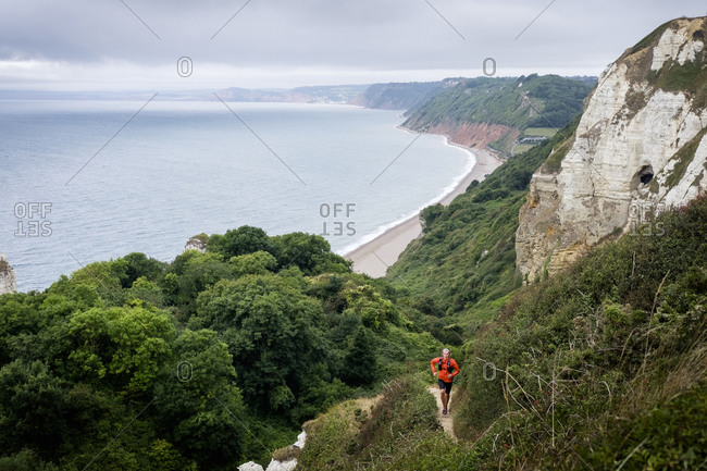 Person trail running, Stairway to Heaven, Jurassic Coast, Devon, England, UK