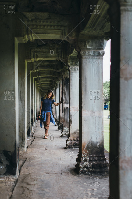 Happy travel photographer exploring ancient ruins of Cambodia