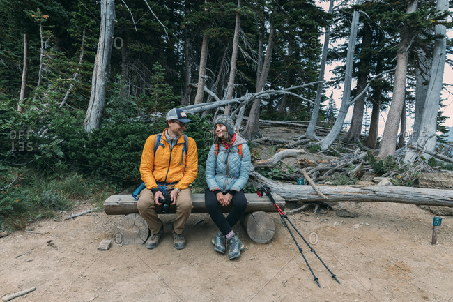 A couple is taking a rest on the mountain trail