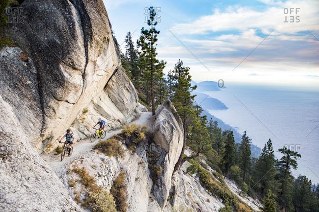 Mountain bikers on mountainside, Flume Trail, Lake Tahoe, Nevada, USA