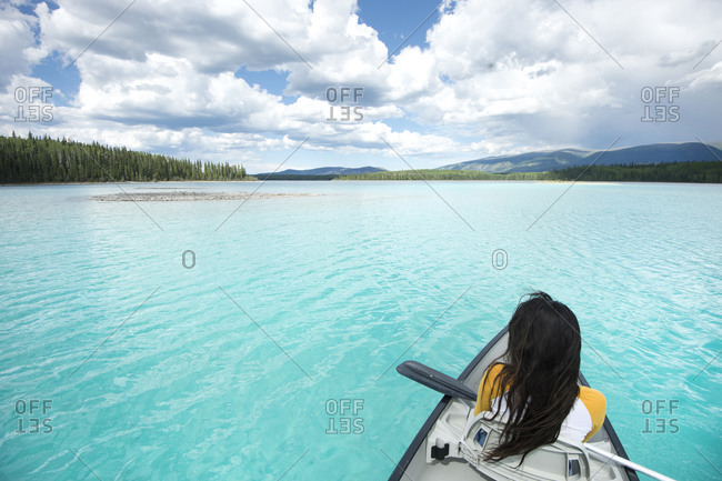High angle view of woman in boat and turquoise water in lake, British Columbia, Canada
