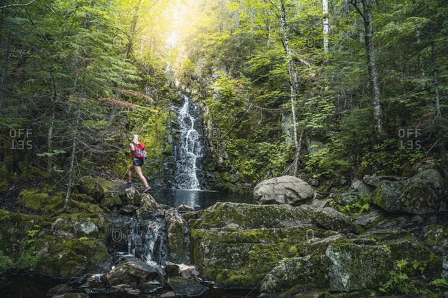 Hiker passing scenic waterfall, Quebec, Canada