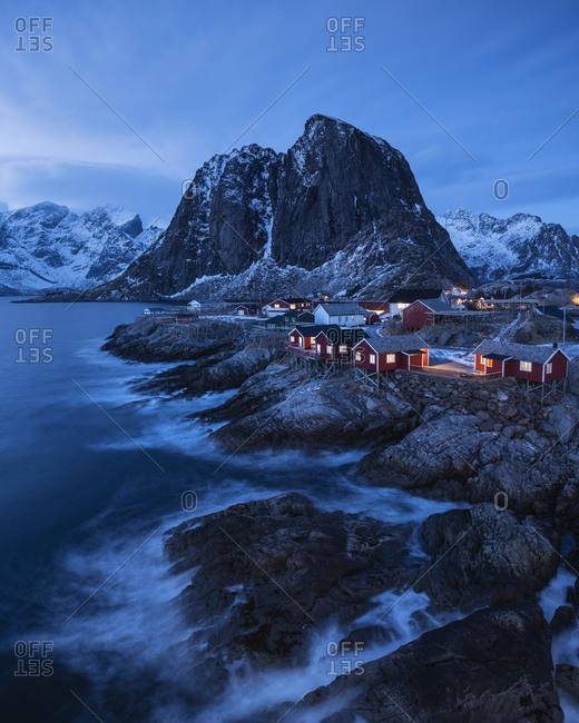 Traditional red Rorbu fishermen cabins on rocky coastline of Hamn, Lofoten Islands, Norway
