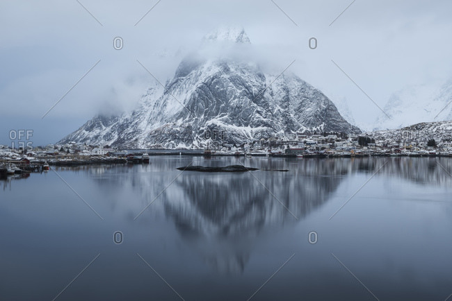 Norway, Lofoten Islands, Reine - February 18, 2018: Winter reflection of Osltind mountain peak in harbor at Reine, Moskenes, Lofoten Islands, Norway