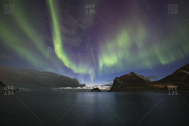 Northern Lights - Aurora Borealis fill sky over Vik beach, Lofoten Islands, Norway