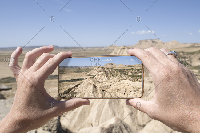 Woman photographing desert landscape with smartphone, Bardenas Reales, Navarra, Spain